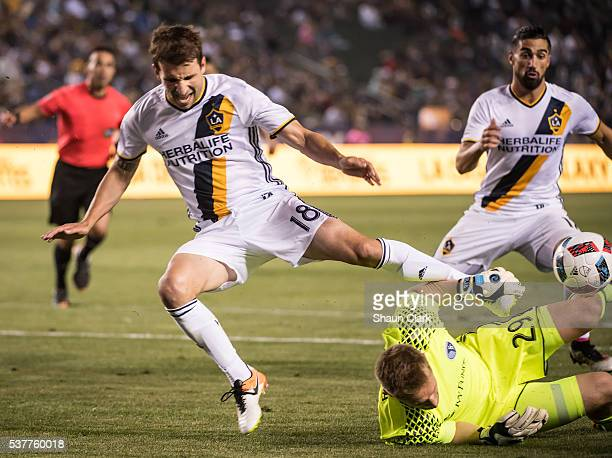 Tim Melia of Sporting Kansas City makes a save as Mike Magee of Los Angeles Galaxy attempts to score during Los Angeles Galaxy's MLS match against...