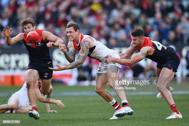Tim Membrey of the Saints handballs whilst being tackled by Joel Smith of the Demons during the round 15 AFL match between the Melbourne Demons and...
