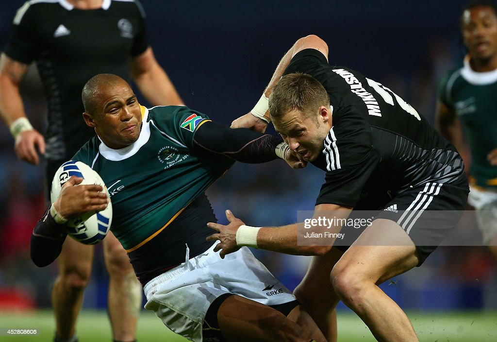 Tim Mikkelson of New Zealand tackles Cornal Hendricks of South Africa during the final match between South Africa and New Zealand at Ibrox Stadium during day four of the Glasgow 2014 Commonwealth Games on July 27, 2014 in Glasgow, United Kingdom.