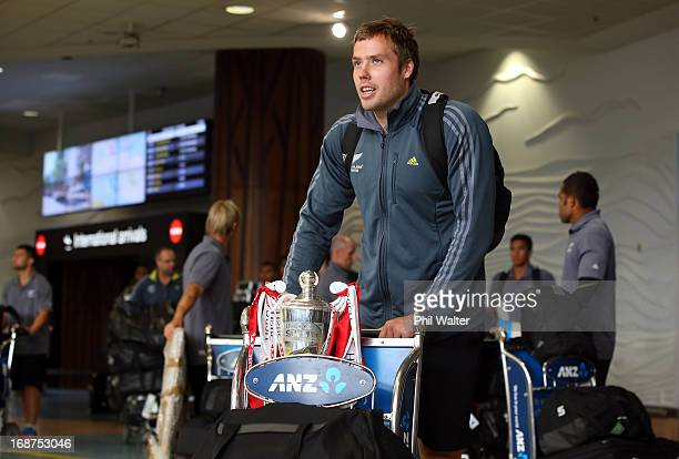 Tim Mikkelson of the New Zealand All Blacks Sevens team arrives at Auckland International Airport with the HSBC Sevens World Series Trophy on May 15...