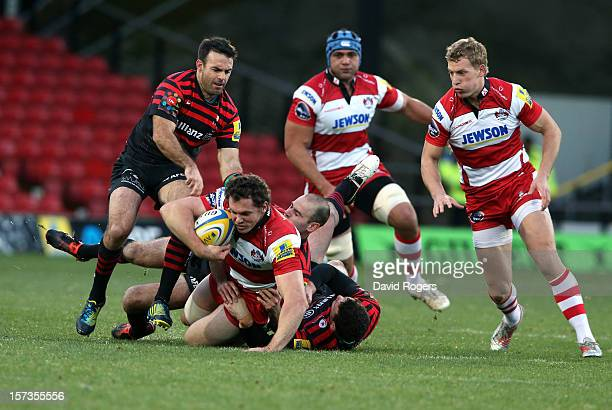 Tim Molenaar of Gloucester is tackled by Neil de Kock and Duncan Taylor during the Aviva Premiership match between Saracens and Gloucester at...