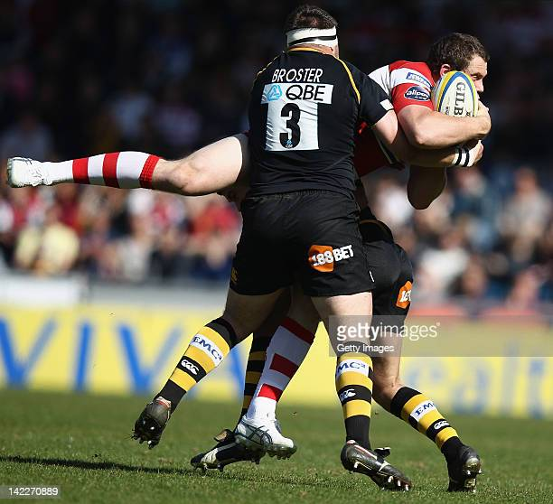 Tim Molenaar of Gloucester Rugby is tackled by Ben Broster and Ryan Davies of London Wasps during the AVIVA Premiership match between London Wasps...