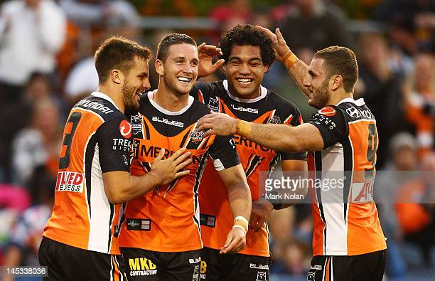 Tim Moltzen of the Tigers is congratulated after scoring during the round 12 NRL match between the Wests Tigers and the North Queensland Cowboys at...