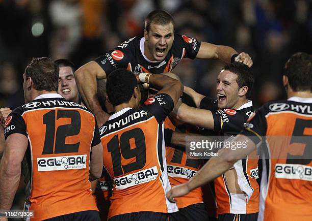 Tim Moltzen of the Tigers jumps on Robbie Farah of the Tigers as he is swamped by his team mates as he celebrates kicking the winning field goal in...