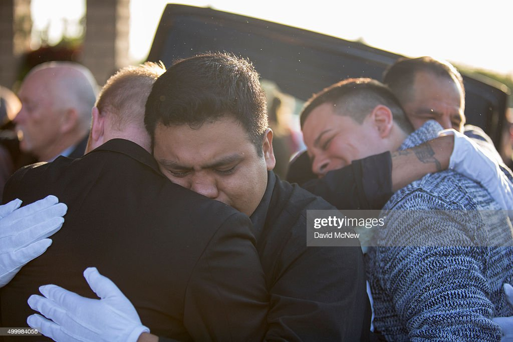 Tim Mraz (far L), boyfriend of Paris attack victim Nohemi Gonzalez, and three other pallbearers hug after carrying her casket from funeral services on December 4, 2015 in Downy, California. Gonzalez, 23, was one of 17 Cal State Long Beach students attending Strate School of Design in Paris as part of a semester abroad program when coordinated attacks that killed 129 people erupted in multiple locales, including the Bataclan theater.