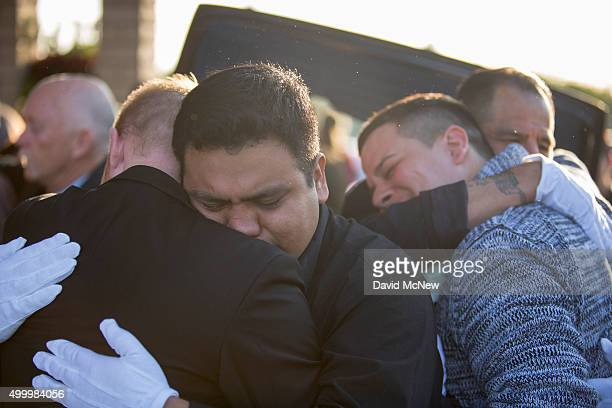 Tim Mraz boyfriend of Paris attack victim Nohemi Gonzalez and three other pallbearers hug after carrying her casket from funeral services on December...