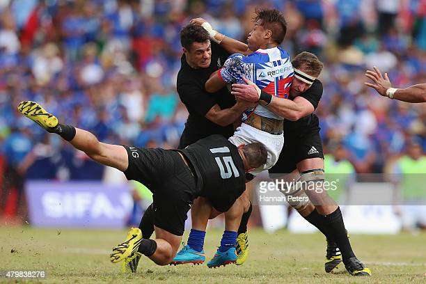 Tim NanaiWilliams of Manu Samoa is hit hard by Daniel Carter of the New Zealand All Blacks during the International Test match between Samoa and the...