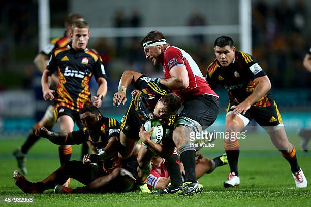 Tim NanaiWilliams of the Chiefs is tackled by Derek Minnie of the Lions during the round 12 Super Rugby match between the Chiefs and the Lions at...