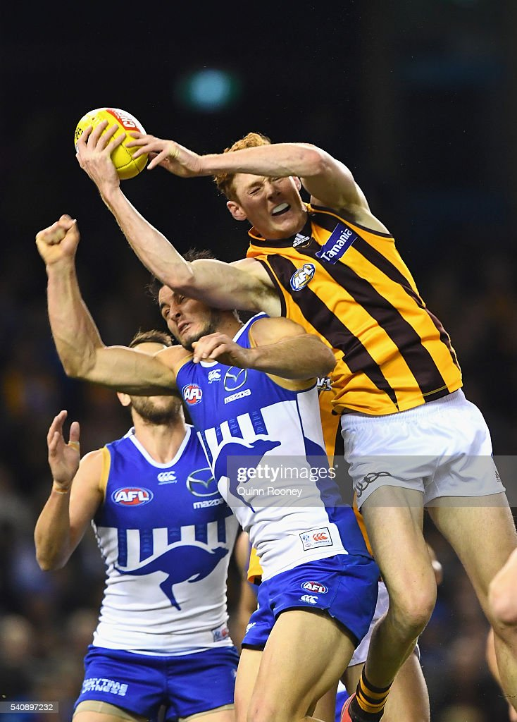 Tim O'Brien of the Hawks attempts to mark over the top of Scott Thompson of the Kangaroos during the round 13 AFL match between the North Melbourne Kangaroos and the Hawthorn Hawks at Etihad Stadium on June 17, 2016 in Melbourne, Australia.