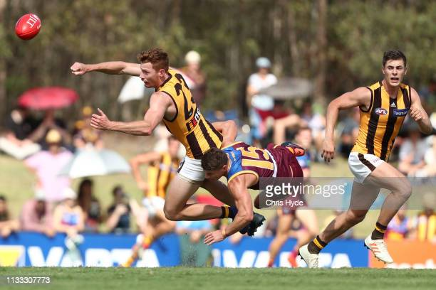 Tim O'Brien of the Hawks handballs while tackled by Dayne Zorko of the Lions during the 2019 JLT Community Series AFL match between the Brisbane...