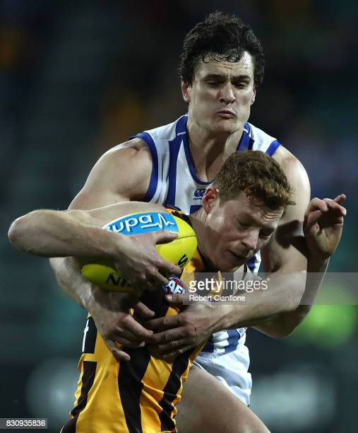 Tim O'Brien of the Hawks is challenged by Scott Thompson of the Kangaroos during the round 21 AFL match between the Hawthorn Hawks and the North...