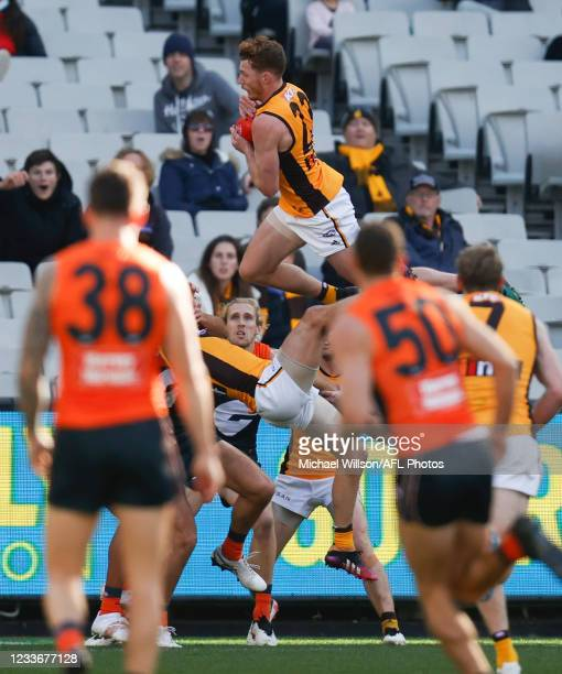 Tim O'Brien of the Hawks takes a spectacular mark over teammate Luke Breust during the 2021 AFL Round 15 match between the GWS Giants and the...