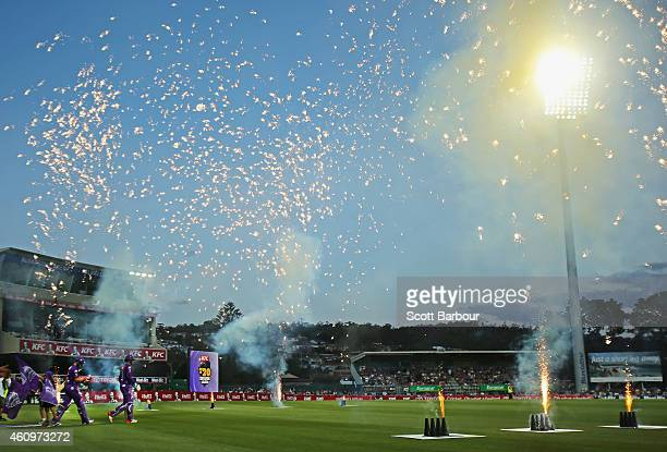 Tim Paine and Ben Dunk of the Hurricanes walk through fireworks out to the middle to open the innings during the Big Bash League match between the...