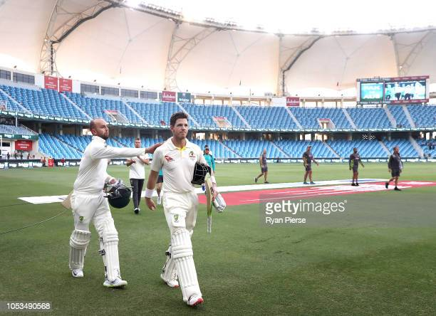 Tim Paine of Australia and Nathan Lyon of Australia celebrate after Australia held on to draw the test match during day five of the First Test match...