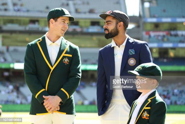 Tim Paine of Australia and Virat Kohli of India talk before the coin toss as Archie Shiller from the Make A Wish foundation who will be co-captain on...