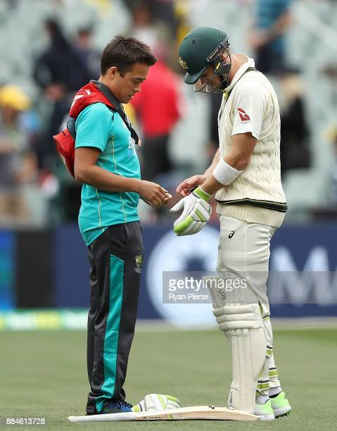 Tim Paine of Australia has his injured finger looked at by Austalian Team Doctor Richard Saw during day two of the Second Test match during the...