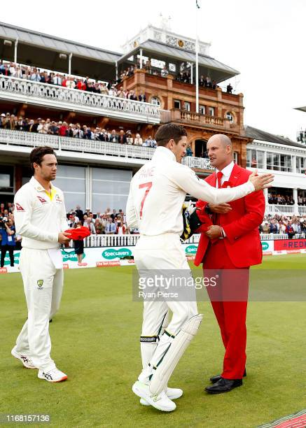 Tim Paine of Australia presents his red cap to Andrew Strauss on Ruth Strauss Day during day two of the 2nd Specsavers Ashes Test between England and...
