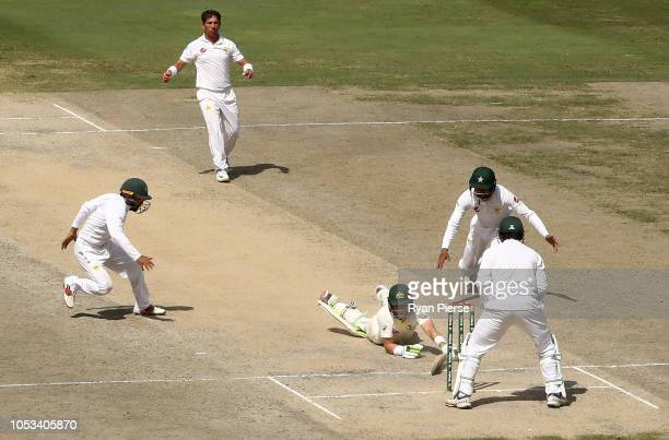 Tim Paine of Australia slips while batting during day five of the First Test match in the series between Australia and Pakistan at Dubai...