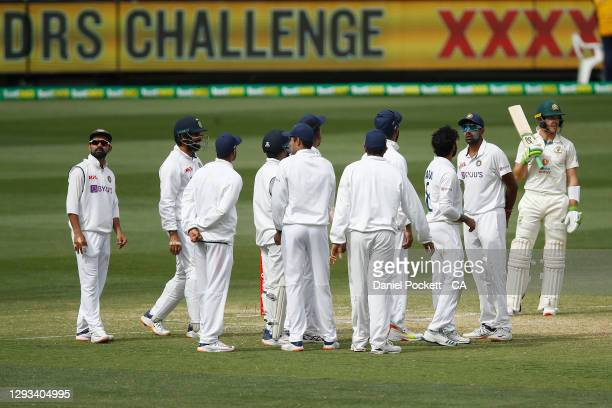 Tim Paine of Australia speaks with Ravindra Jadeja of India whilst the challenge for his wicket is reviewed during day three of the Second Test match...