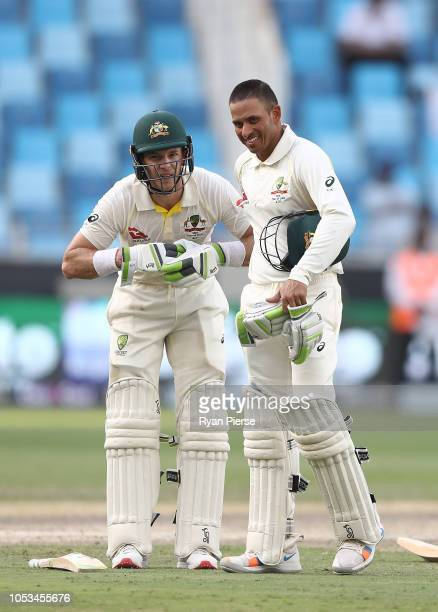 Tim Paine of Australia speaks with Usman Khawaja of Australia during day five of the First Test match in the series between Australia and Pakistan at...