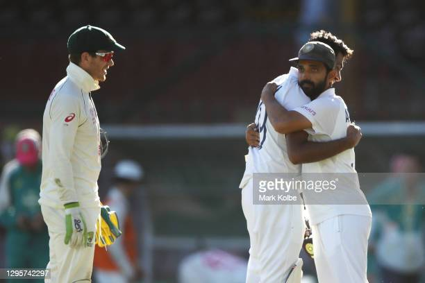 Tim Paine of Australia watches on as Ravichandran Ashwin of India embraces his captain Ajinkya Rahane of India as they celebrate securing a draw...