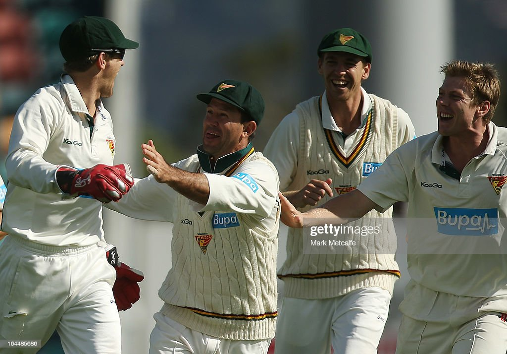 Tim Paine (L) of the Tigers celebrates with teammates Ricky Ponting, Luke Butterworth and James Faulkner after taking a catch to dismiss Joe Burns of the Bulls during day three of the Sheffield Shield final between the Tasmania Tigers and the Queensland Bulls at Blundstone Arena on March 24, 2013 in Hobart, Australia.