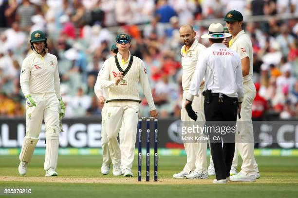Tim Paine Steve Smith Nathan Lyon and Pat Cummins of Australia look at umpire Chris Gaffaney after calling successfully for DRS referral for the...