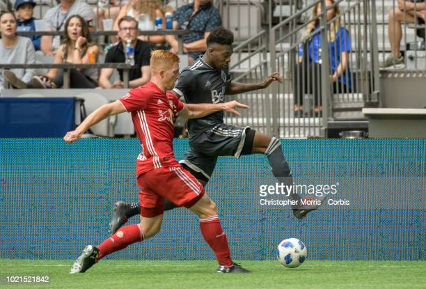 Tim Parker of New York Red Bulls and Alphonso Davies of Vancouver Whitecaps compete for the ball at BC Place on August 18 2018 in Vancouver Canada