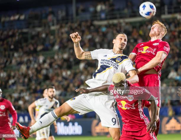 Tim Parker of New York Red Bulls heads the ball as Zlatan Ibrahimovic of Los Angeles Galaxy attacks during the Los Angeles Galaxy's MLS match against...