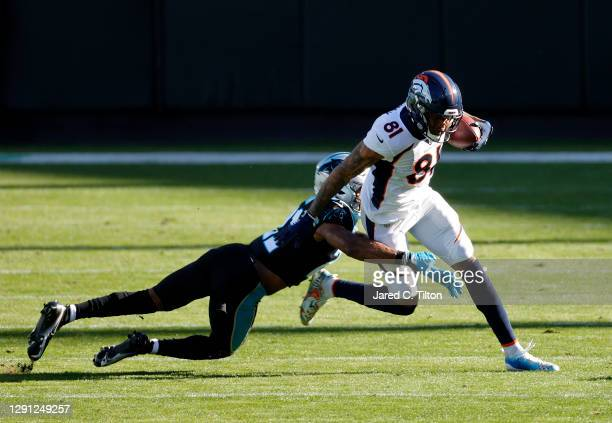 Tim Patrick of the Denver Broncos attempts to break a tackle from Jeremy Chinn of the Carolina Panthers during the second quarter of their game at...