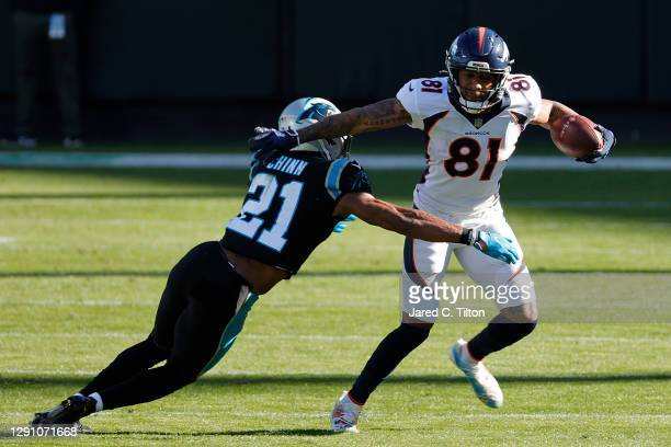 Tim Patrick of the Denver Broncos carries the ball against Jeremy Chinn of the Carolina Panthers during the second quarter at Bank of America Stadium...