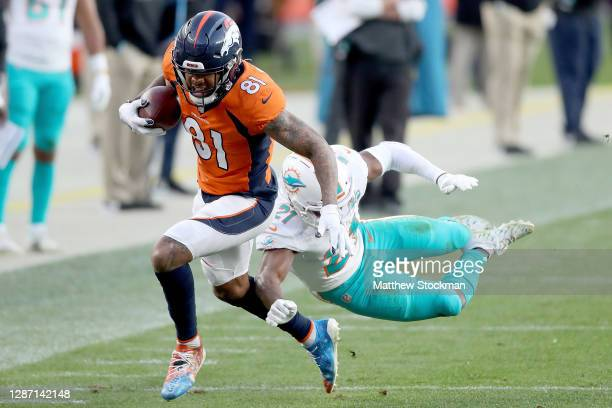 Tim Patrick of the Denver Broncos runs after his catch as he is chased from behind by Eric Rowe of the Miami Dolphins during the third quarter at...