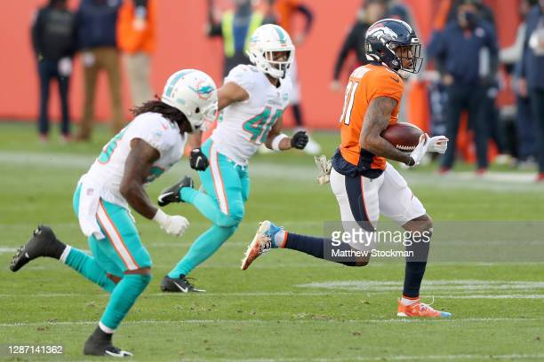 Tim Patrick of the Denver Broncos runs after his catch for a 41 yard gain between Bobby McCain and Nik Needham of the Miami Dolphins during the...