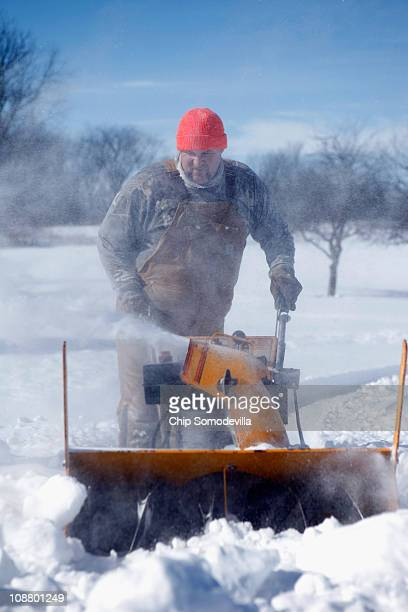 Tim Peterson uses a snowblower to clear his driveway after more than 14 inches of snow fell on parts of eastern Iowa February 3 2011 in Massillon...
