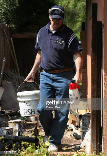 Tim Phillips assistant manager and biologist with the Fresno Mosquito and Vector Control District walks towards the backyard carrying a bucket of...
