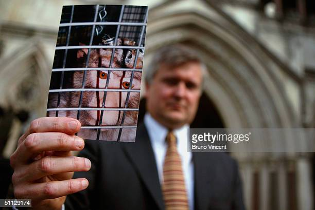 Tim Phillips from the National Anti-Vivisection Society holds up a photo of a caged monkey as he arrives at the Royal Courts of Justice to challenge...