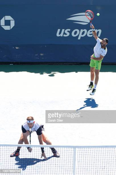 Tim Puetz of Germany serves the ball as doubles partner Michael Venus of New Zealand looks on during their Men's Doubles first round match against...