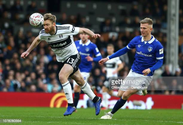 Tim Ream of Fulham FC head the ball from Sam Surridge of Oldham Athletic during the FA Cup third round match between Fulham FC and Oldham Athletic...
