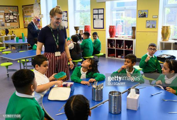 Tim Roach Vice Principal and Ruth Titmuss class teacher wear PPE face shields as they supervise Year Four children eating lunch at Greenacres Primary...