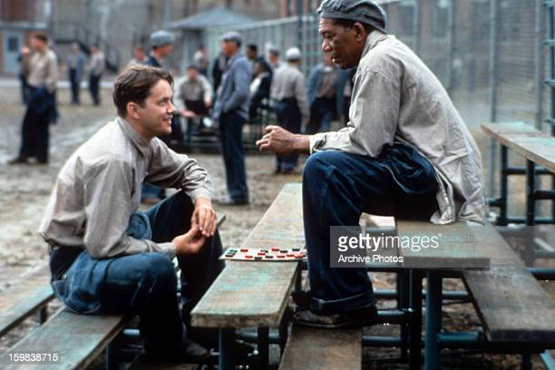 Tim Robbins and Morgan Freeman sitting outside on the benches playing checkers and talking in a scene from the film 'The Shawshank Redemption' 1994