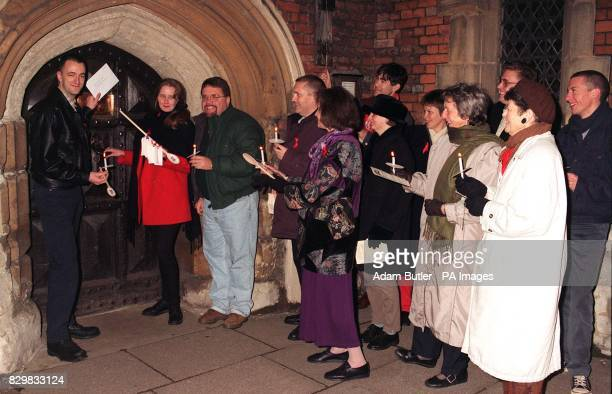 Tim Robertson and Rachel Carr of AGLO are joined by protestors outside Lambeth Palace London this evening as they prepare to deliver a signed wooden...
