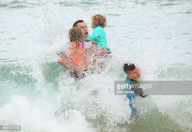 Tim Sachar holds tightly onto his daughters Ava and Maya whilst in the surf at Bondi Beach on December 25 2015 in Sydney Australia Bondi Beach is a...