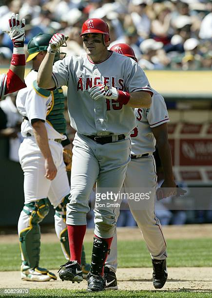 Tim Salmon of the Anaheim Angels celebrates with a teammate at home plate during the MLB game against the Oakland A's at Network Associates Coliseum...