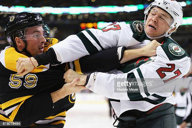 Tim Schaller of the Boston Bruins and Zac Dalpe of the Minnesota Wild fight during the first period at TD Garden on October 25 2016 in Boston...