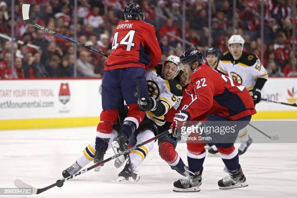 Tim Schaller of the Boston Bruins is checked by Brooks Orpik of the Washington Capitals during the first period at Capital One Arena on December 28...