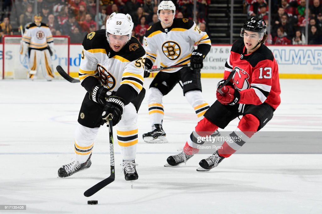 Tim Schaller #59 of the Boston Bruins is pursued by Nico Hischier #13 of the New Jersey Devils at Prudential Center on February 11, 2018 in Newark, New Jersey. The Boston Bruins defeated the New Jersey Devils 5-3.
