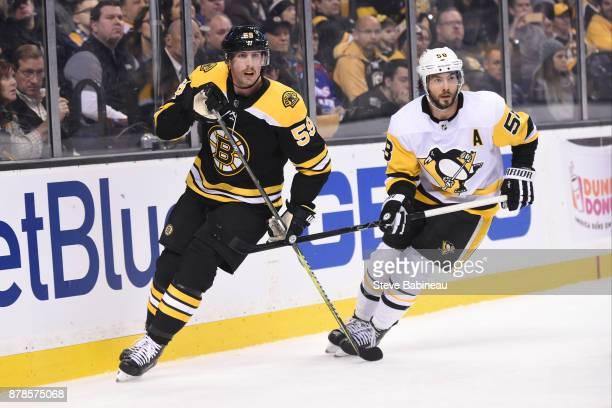Tim Schaller of the Boston Bruins skates against Kris Letang of the Pittsburgh Penguins at the TD Garden on November 24 2017 in Boston Massachusetts