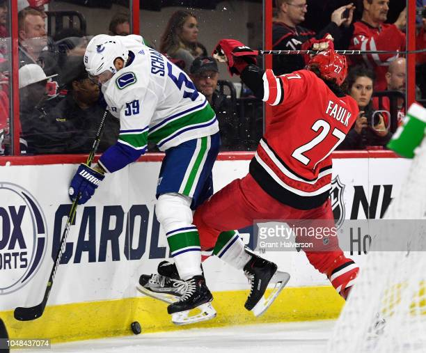 Tim Schaller of the Vancouver Canucks battles Justin Faulk of the Carolina Hurricanes for the puck during the second period of their game at PNC...
