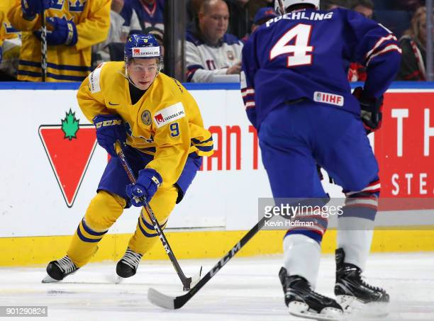 Tim Sderlund of Sweden skates up ice with the puck in the first period as Ryan Poehling of United States defends during the IIHF World Junior...