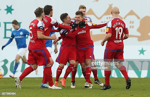 Tim Siedschlag of Kiel jubilates with team mates after scoring the third goal during the third league match between FC Hansa Rostock and Holstein...